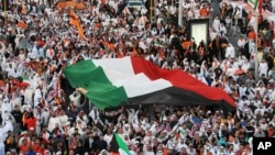 Islamist, nationalist and liberal opposition groups carry a large national flag as they gather to protest the Kuwait government's amendment of the electoral law and support a boycott on the country's election on November 30, 2012 in Kuwait City.