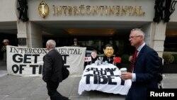 """总部设在伦敦的支持藏人权利团体""""自由西藏""""在洲际酒店门前示威,有人戴着习近平和洲际酒店集团首席执行官的面具。(2013年8月5日)"""