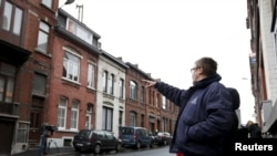 """A resident points at a house located in a street called """"Rue du Fort"""" in Charleroi, Belgium, Jan. 13, 2016."""