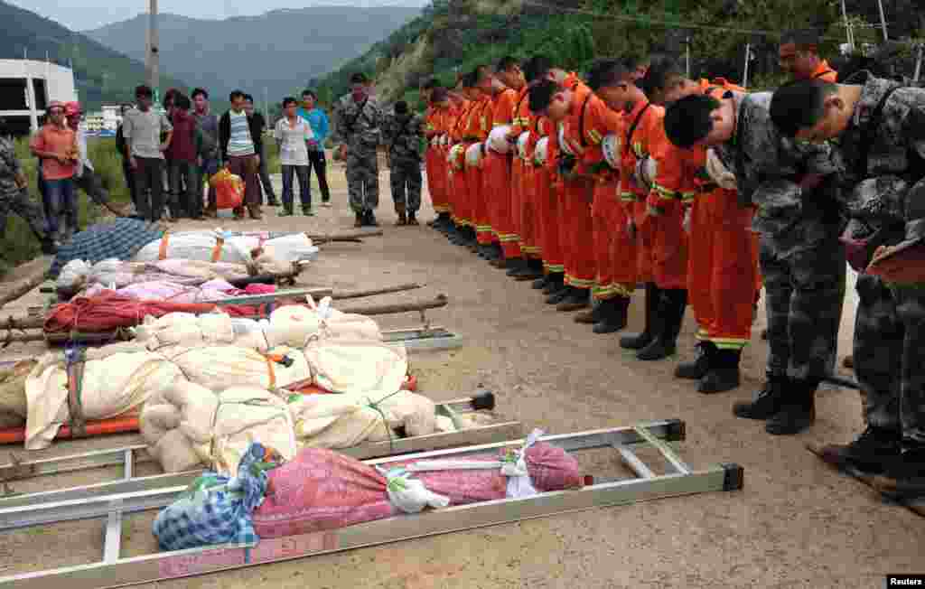 Rescuers bow to pay tribute to residents who were killed during an earthquake in Longtoushan township, Ludian county, Yunnan province, Aug. 4, 2014.