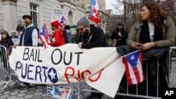 FIL E - Protesters express their opposition to the fact the the Federal Reserve bank bailed out Wall Street but not Puerto Rico outside International House, in New York, April 7, 2016.