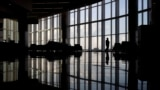 FILE - In this June 1, 2020 file photo, a woman looks through a window at a near-empty terminal at an airport in Atlanta. A new survey found that the coronavirus pandemic has taken a harsh toll on the mental health of young Americans. (AP Photo/Charlie Riedel, File)