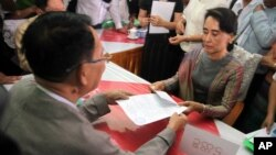 Myanmar opposition leader Aung San Suu Kyi, right, submits her documents for the upcoming general election at an election commission office on the outskirts of Yangon, Myanmar, July 29, 2015.