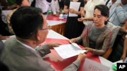 FILE - Myanmar opposition leader Aung San Suu Kyi, right, submits her documents for the upcoming general poll, election commission office, Yangon, Myanmar, July 29, 2015.