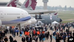 Visitors walk by a Boeing 777-300ER at left, and and Airbus A400M, at right, during the Paris Air Show, at Le Bourget airport, east of Paris, June 15, 2015.