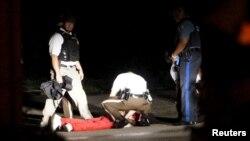 미국 미주리주 퍼거슨 시에서 흑인 사망 사건 1주년 행사가 열린 9일 총격전이 발생한 가운데, 경찰이 쏜 총에 맞은 남성이 바닥에 쓰러져 있다.