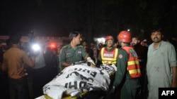 巴基斯坦救援人员从该国东部城市拉合尔一处游人众多的公园搬运尸体(2016年3月27日)