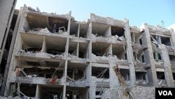 Pasukan keamanan Suriah memeriksa gedung dinas intelijen pasca serangan bom di Damaskus (17/3).