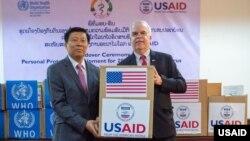 U.S. Ambassador Peter Haymond hands PPE equipment to Deputy Minister Phouthone Muongpak of Laos.
