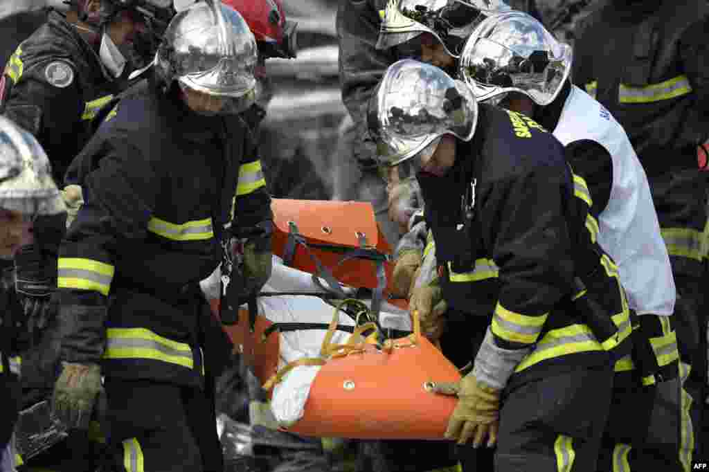 Firefighters carry a body found in the rubble of a four-story residential building which collapsed following a blast in Rosny-sous-Bois in the eastern suburbs of Paris, France.