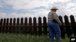 "FILE -In this Sept. 16, 2015, photo, farmer Fausto Salinas stands along the border fence, in McAllen, Texas. The staggered fence or ""wall,"" costing $6.5 million per mile, runs along some 100 miles of Texas' 1,254-mile border with Mexico."