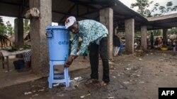 Un homme se lave les mains avec de l'eau provenant d'un distributeur contenant de l'eau mélangée à du désinfectant au Congo Air Market sur la route de l'aéroport à l'est de Mbandaka le 23 mai 2018.