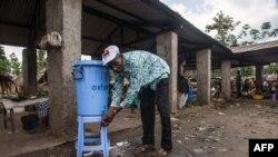 Un homme se lave les mains avec de l'eau provenant d'un distributeur contenant de l'eau mélangée à du désinfectant au Congo Air Market sur la route de l'aéroport à l'est de Mbandaka, le 23 mai 2018. (Photo: Junior D. KANNAH/AFP)