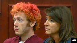 星期五科羅拉多州電影院槍擊案嫌疑人詹姆斯•霍姆斯(左)星期一和他的律師塔瑪拉•布雷迪在科羅拉多州的一個法庭第一次出庭