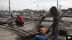 Nigerian refills a small generator on the rooftop of his store in Oshodi Market in Lagos in March, 2010. Despite rich oil resources, much of the nation's economy depends on provide generators for power.