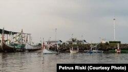 Perahu dan kapal penangkap ikan milik nelayan Muncar, Banyuwangi, berada di pelabuhan Muncar yang dikelilingi tanggul pelindung ombak, 5 Januari 2019. (Foto: Petrus Riski/VOA)