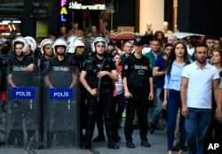Turkish police officers secure central Istanbul's Istiklal Avenue, the main shopping road, as protesters stage a demonstration against a decision by Turkey's parliament to amend the constitution, May 20, 2016.