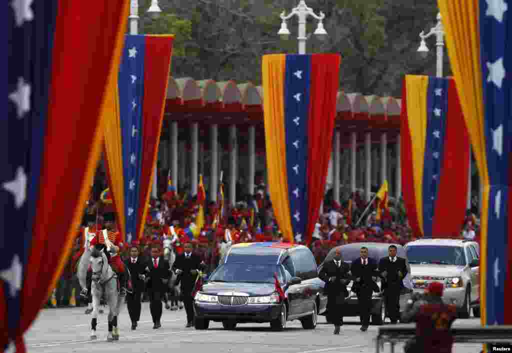 Guards run next to the hearse holding the body of Venezuela's late President Hugo Chavez during his funeral parade in Caracas. Hundreds of thousands of Venezuelans were on the streets for parade amid opposition protests that the government was exploiting president's death for election purposes.