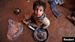 Một đứa trẻ tị nạn Syria ăn bên trong lều của gia đình mình tại một khu định cư không chính thức ở Deir al-Ahmar, thung lũng Bekaa.