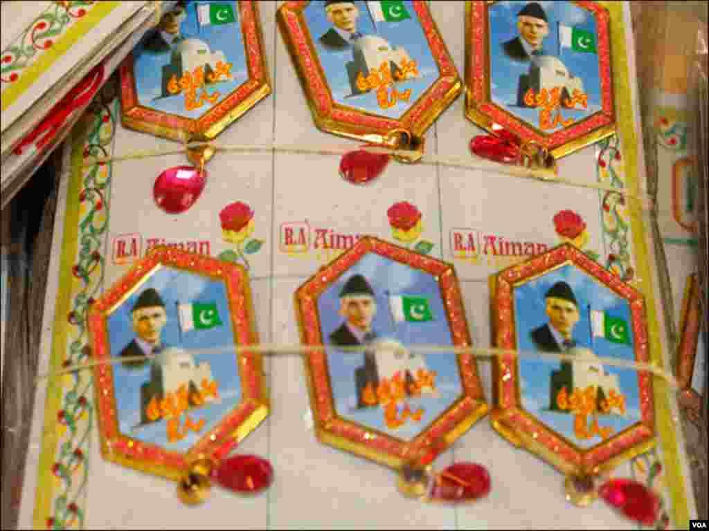 ایک اسٹال پر رکھے بانی پاکستان قائداعظم کی تصویر اور سبز پرچم والے بیجز