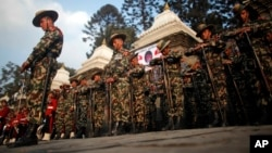FILE - Nepalese army soldiers give a guard of honor during the cremation of Nepalese prime minister Sushil Koirala, on the banks of the Bagmati River in Kathmandu, Nepal. Nepal will hold its first-ever military exercise with China next month.