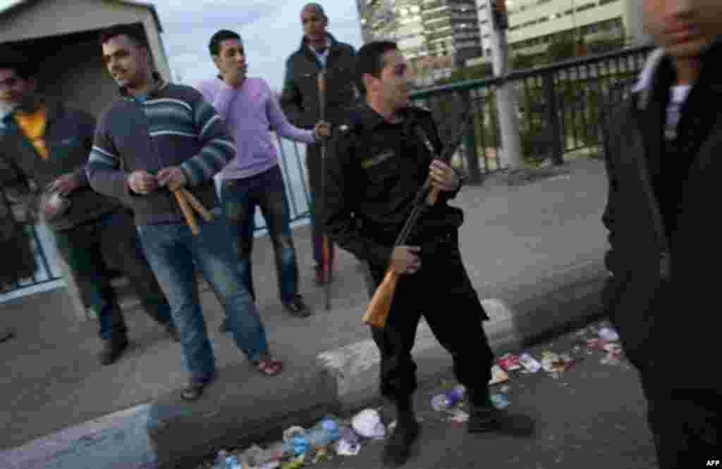 An Egyptian police officer stands guard next to one of the many neighborhood watch groups of men armed with metal bars and sticks at a checkpoint leading to a bridge in Cairo, Egypt, Monday, Jan. 31, 2011. A coalition of opposition groups called for a mi