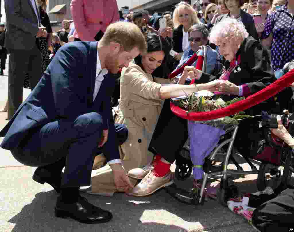 Britain's Prince Harry and Meghan, Duchess of Sussex, meet 98-year-old Daphne Dunne during a walkabout outside the Opera House in Sydney, Australia. Prince Harry and his wife Meghan are on a 16-day tour of Australia and the South Pacific.