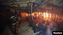 Para petugas pemadam kebakaran di dalam sebuah pabrik garmen di Gazipur, Bangladesh (9/10). (Reuters/Andrew Biraj)