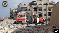 "In this photo provided by the Syrian Civil Defense group known as the ""White Helmets,"" a destroyed ambulance is seen outside the Syrian Civil Defense main center after airstrikes in Ansari neighborhood in the rebel-held part of eastern Aleppo, Syria, Sept"