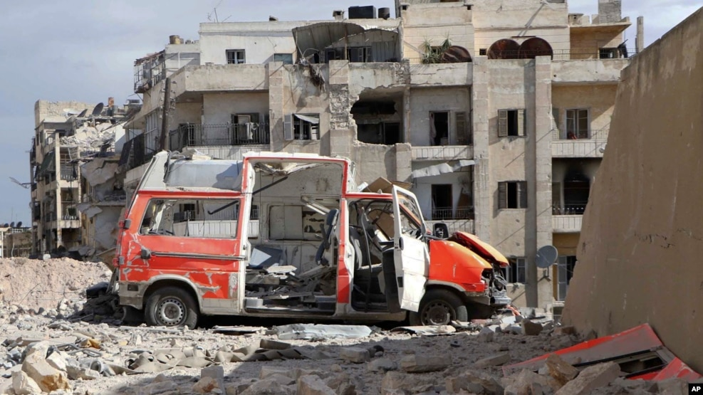 """In this photo provided by the Syrian Civil Defense group known as the """"White Helmets,"""" a destroyed ambulance is seen in the Ansari neighborhood in the rebel-held part of eastern Aleppo, Syria, Sept. 23, 2016."""