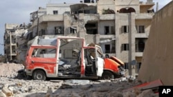 "In this photo provided by the Syrian Civil Defense group known as the ""White Helmets,"" a destroyed ambulance is seen in the Ansari neighborhood in the rebel-held part of eastern Aleppo, Syria, Sept. 23, 2016."