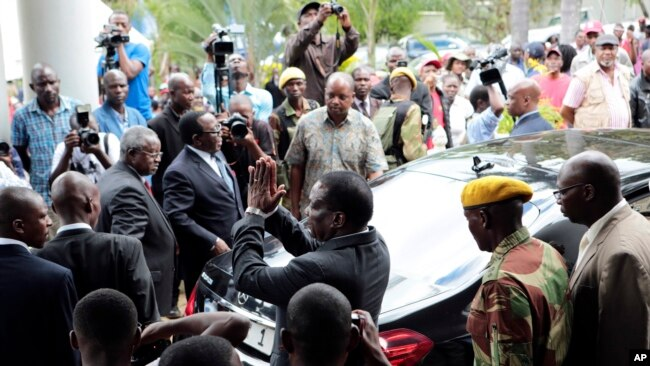 FILE - Zimbabwe President Emmerson Mnangagwa, center, leaves after paying his respects to the family of Morgan Tsvangirai, in Harare, Feb. 18, 2018.