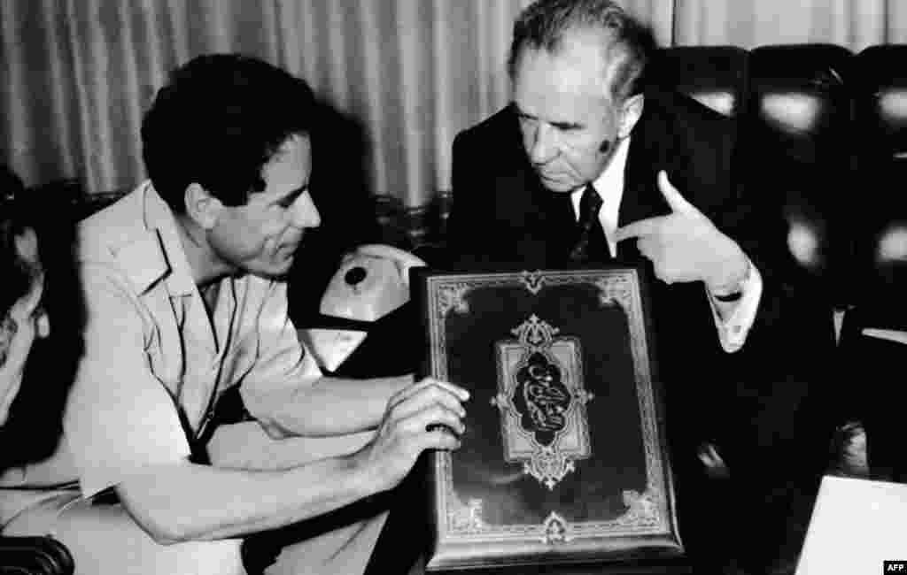 Files of Libyan Col. leader Moammar Kadhafi (L) receives an old copy of Koran from Alexei Kossyguine, 12 May 1975