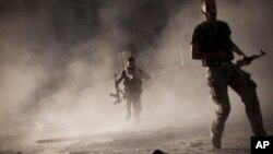 In this Friday, Sept 7, 2012 photo, Free Syrian Army fighters run after attacking a Syrian Army tank during fighting in the Izaa district in Aleppo, Syria.