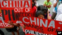 FILE - Protesters display placards during a rally at the Chinese consulate in the financial district of Makati city, east of Manila, Philippines, Nov. 12, 2015.