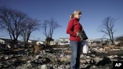 Seorang penyintas berdiri di atas reruntuhan rumahnya yang, bersama lebih dari 50 rumah lain, terbakar pada saat super badai Sandy. (Foto: Dok)