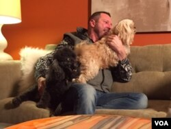Bobby's dogs scamper into his lap at his home in Kansas. The Affordable Care Act pays for expensive prescriptions that keep Bobby alive. He agrees the law isn't perfect but hopes Congress doesn't eliminate it. (C. Presutti/VOA)
