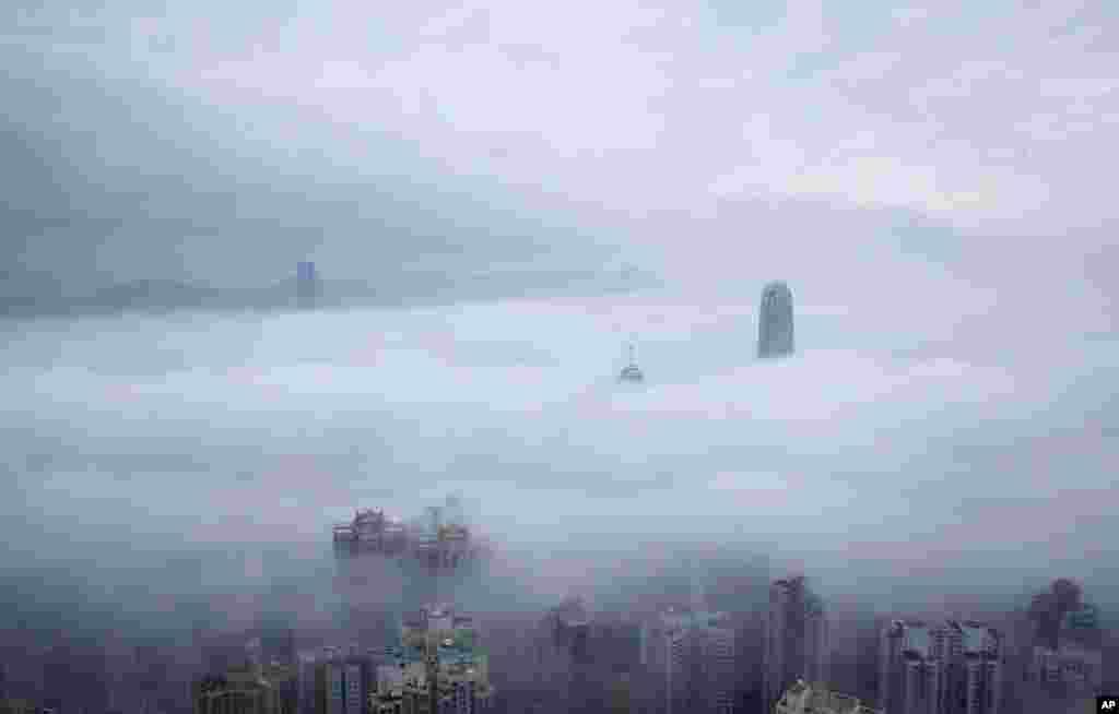برج مرکز مالی بینالمللی (وسط-راست) و برج مرکز تجارت بینالمللی (بالا و چپ)، از فراز ابرها در هنگ کنگ دیده میشوند.