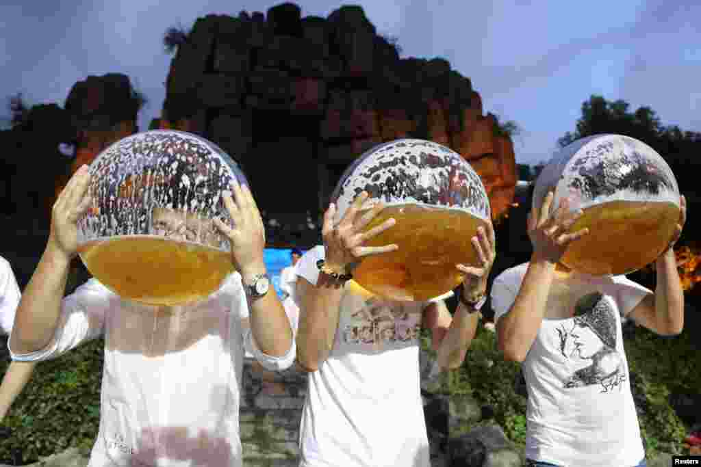 People drink beer from fish bowls at a beer drinking competition in Hangzhou, Zhejiang province, China, July 21,2018.