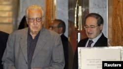 Syria's Deputy Foreign Minister Faisal Mekdad (R) welcomes U.N.-Arab League peace envoy for Syria Lakhdar Brahimi at a hotel in Damascus, October 19, 2012.