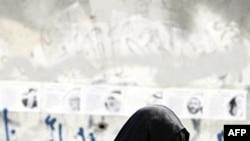 """Phụ nữ Bahrain đi ngang qua bức tường với hàng chữ viết bên dưới hình ảnh các lãnh đạo đối lập bị bắt giữ: """"Thượng đế phóng thích cho các tù nhân của chúng tôi"""""""