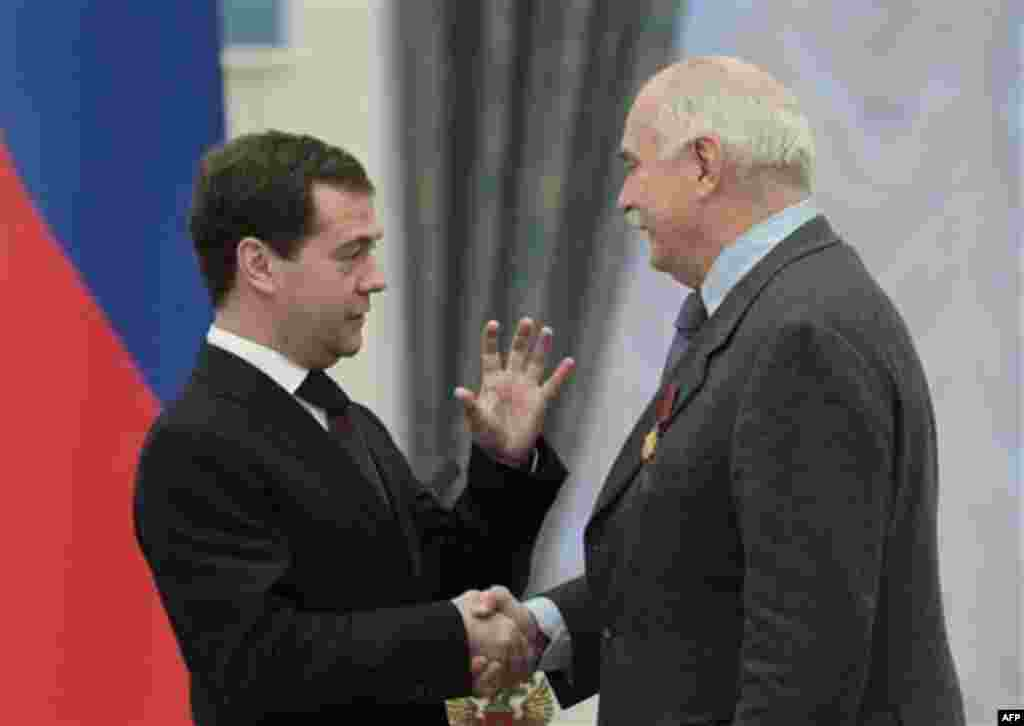 Russian President Dmitry Medvedev, left, presents famous Russian filmmaker and actor Nikita Mikhalkov with a medal during an award ceremony in the Kremlin in Moscow, Thursday, Dec. 30, 2010. (AP Photo/Alexander Natruskin, Pool)