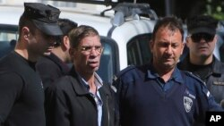EgyptAir plane hijacking suspect Seif Eddin Mustafa, second left, is escorted by Cyprus police officers as he leaves a court after a remand hearing as authorities investigate him on charges including hijacking, illegal possession of explosives and abduction in the Cypriot coastal town of Larnaca, March 30, 2016.