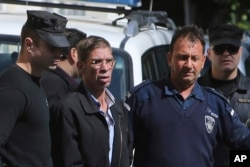 EgyptAir plane hijacking suspect Seif Eddin Mustafa, second left, is escorted by Cyprus police officers as he leaves a court after a remand hearing as authorities investigate him on charges including hijacking, illegal possession of explosives and abduction in the Cypriot coastal town of Larnaca Wednesday, March 30, 2016.