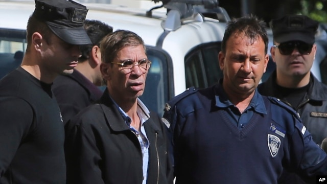 "EgyptAir plane hijacking suspect Seif Eddin Mustafa, second left, is escorted by Cyprus police officers as he leaves a court after a remand hearing as authorities investigate him on charges including hijacking, illegal possession of explosives and abduction in the Cypriot coastal town of Larnaca Wednesday, March 30, 2016. Mustafa described as ""psychologically unstable"" hijacked a flight Tuesday from Egypt to Cyprus and threatened to blow it up. His explosives turned out to be fake, and he surrendered with all passengers released unharmed after a bizarre six-hour standoff."