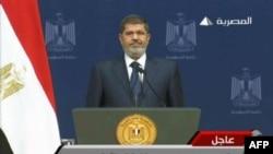 6月26日电视画面显示穆尔西站在埃及开罗电视台的讲坛上准备就自己执政一周年向全国发表演说。