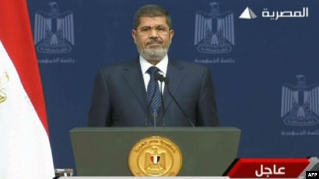 An image  taken from Egyptian state TV shows Egyptian President Mohamed Morsi standing on the podium ahead of his televised address to the nation on his first year in power, in Cairo, June 26, 2013.