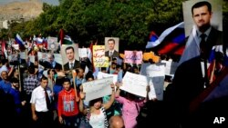 Şam'daki Rus büyükelçiliğine saldırının ardından gösteri düzenleyen ve ellerinde Rus ve Suriye bayraklarıyla Beşar Esat'la Vladimir Putin'in resimlerini taşıyan rejim yanlısı göstericiler.