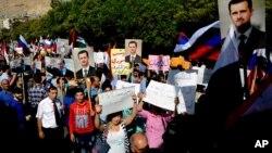 Warga Suriah membawa foto Presiden Rusia Vladimir Putin dan Presiden Suriah Bashar al-Assad di depan Kedutaan Rusia di Damaskus untuk menunjukkan rasa terimakasih atas dukungan Rusia terhadap Suriah, pasca serangan roket oleh militan hari Selasa (13/10).