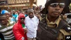 Le leader de l'opposition et candidat à la présidence Kizza Besigye, au centre, est arrêté par la police antiémeute après avoir tenté de marcher avec ses partisans le long d'une rue dans le centre de Kampala, en Ouganda, 15 février 2016.